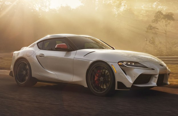 Shiny white 2020 Toyota Supra cruises down a street drenched with golden sun.