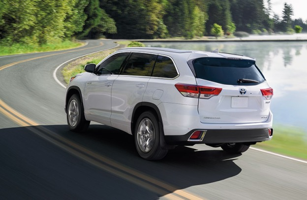 A white 2019 Toyota Highlander drives on a curvy highway near a placid lake.
