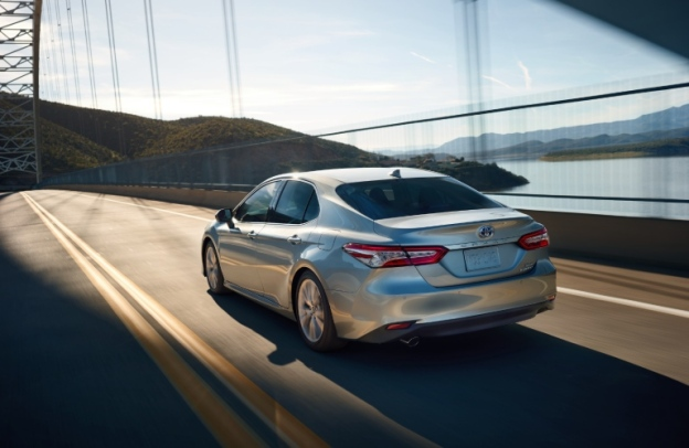 2020 Toyota Camry Hybrid drives across a bridge.