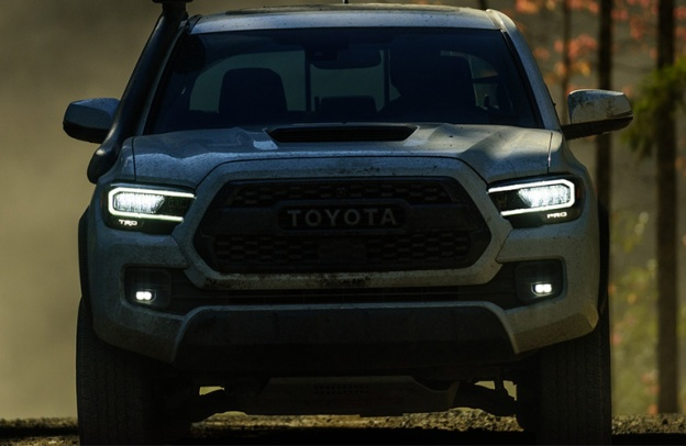 Head-on view of an imposing 2020 Toyota Tacoma looming in the shadows.