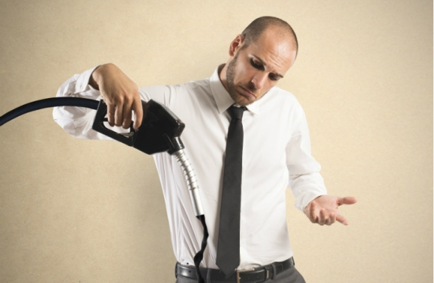 A man dressed in business casual attire shrugs as black fluid pours from a gas nozzle onto the floor and his pants.