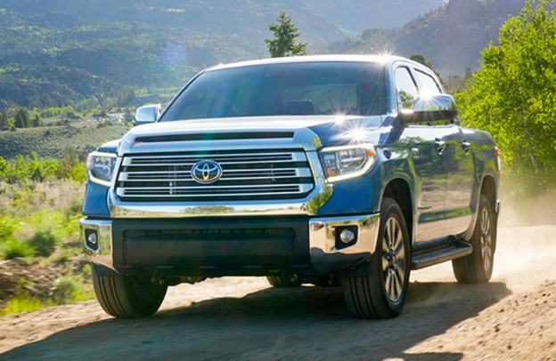 Blue 2020 Toyota Tundra drives ruggedly along a trail.
