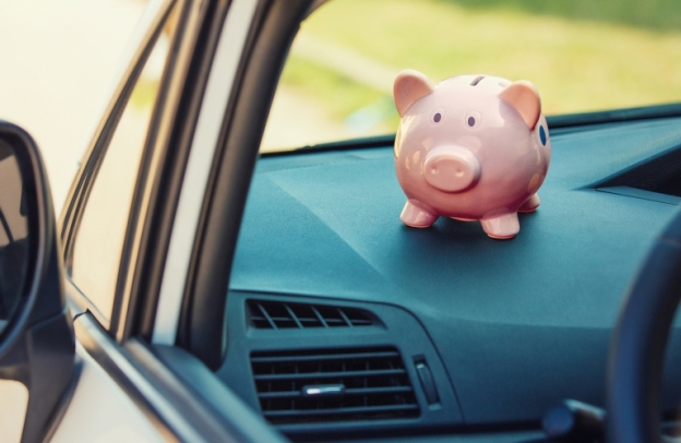 A cute pink piggy bank sits perched on the dashboard, symbolizing the financial side of vehicle ownership