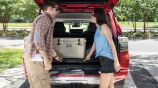 Couple loads a cooler in the back and lifts the hidden rear floor of the 2020 Toyota 4Runner