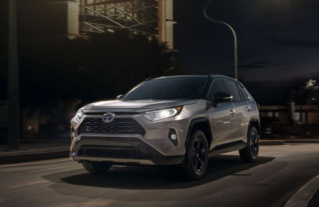 Silver 2020 Toyota RAV4 drives up a road at night