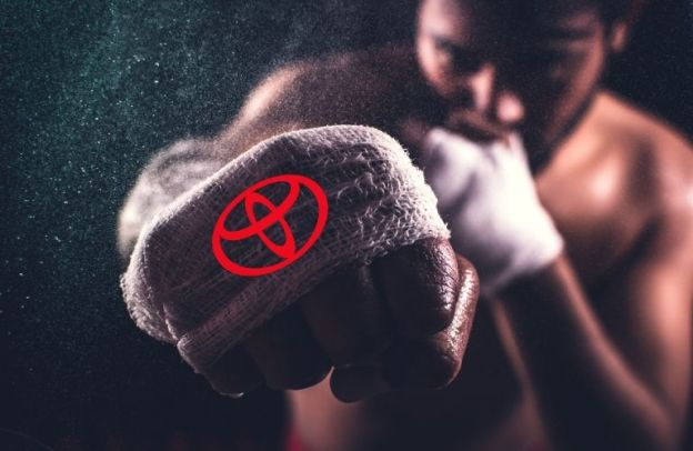 "A man punches forward with the ""Toyota"" logo emblazoned on his knuckles"