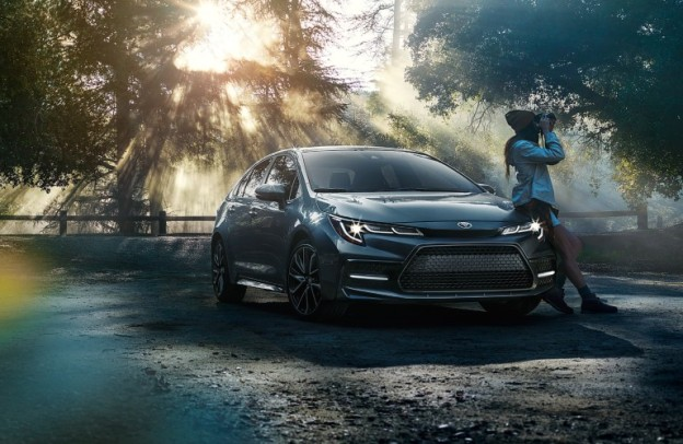 Woman with a camera leans against a 2021 Toyota Corolla