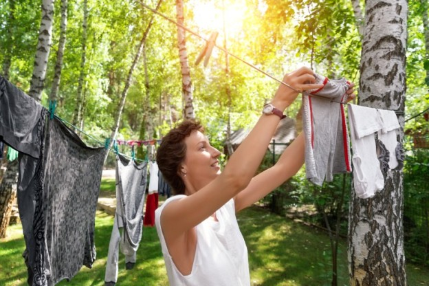 Woman hangs clothes on a clothesline amongst trees