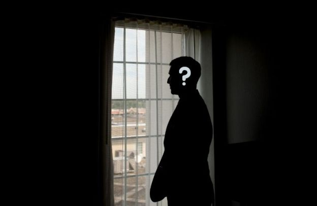 Mysterious silhouette of a man with a question mark on his head