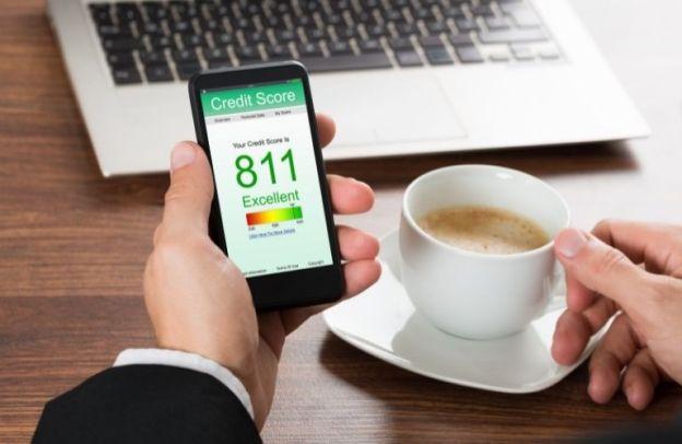 Man with espresso checks credit score