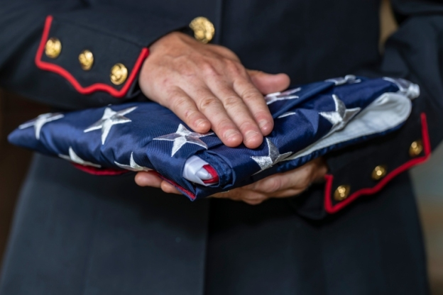Soldier holds American flag folded in her hands